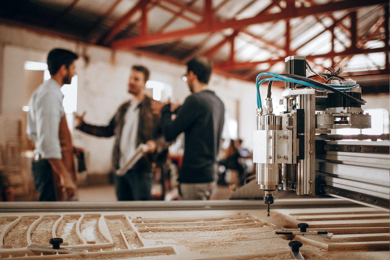Three business men talking in background behind large industrial machine.